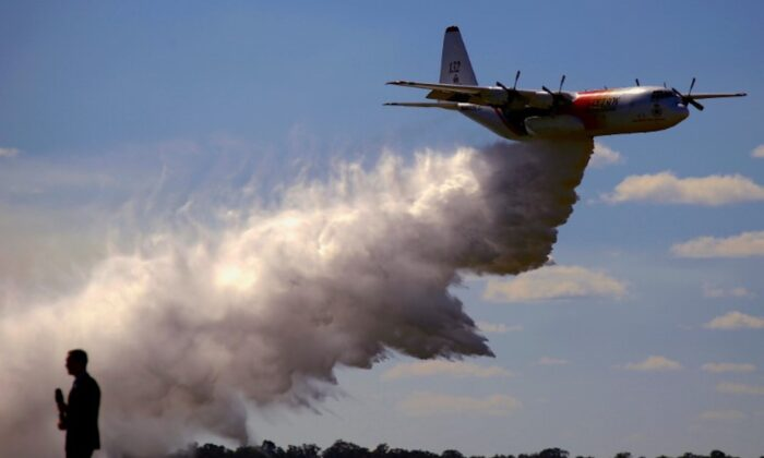 File photo: A television reporter stands in front of a Large Air Tanker (LAT) C-130 Hercules as it drops a load of around 15,000 litres during a display by the Rural Fire Service ahead of the bushfire season at RAAF Base Richmond  Sydney, Australia, Sept. 1, 2017.  (Reuters/David Gray/File Photo)