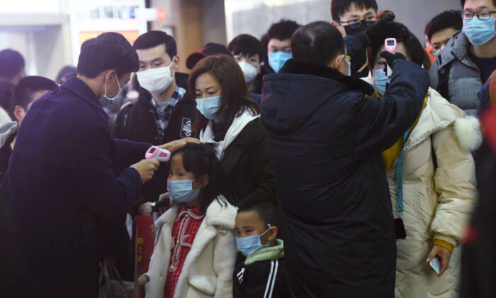 Staff members check body temperatures of the passengers arriving from the train from Wuhan to Hangzhou, at Hangzhou Railway Station ahead of the Chinese Lunar New Year in Zhejiang Province, China on Jan. 23, 2020. (China Daily via Reuters)