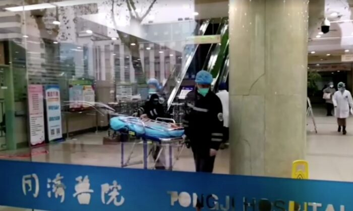 People wearing masks work at a hospital in Wuhan, Hubei province, China on Jan. 23, 2020, in this still image taken from video. (China News Service/via Reuters TV)