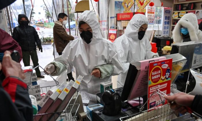 Pharmacy workers wearing protective clothes and masks serve customers in Wuhan on Jan. 25, 2020. (Hector Retamal/AFP via Getty Images)