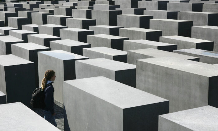 A visitor walks among the 2,711 stellae at the Memorial to the Murdered Jews of Europe on the first day of its opening to the public in Berlin, Germany, on May 12, 2005. The monument, a Holocaust memorial, was designed by American architect Peter Eisenman and commemorates the 6 million Jews murdered by the Nazis. The memorial has been a controversial project in the heart of Berlin 17 years in the making.  Sean Gallup/Getty Images