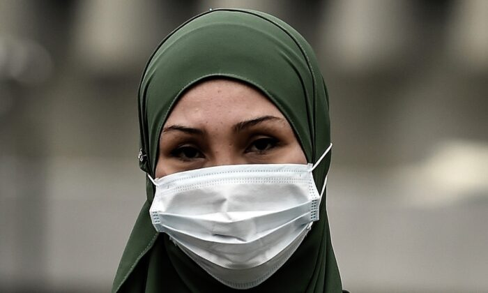 A Malaysian Muslim woman wearing a face-mask crosses a road during thick haze over Kuala Lumpur on Sept. 15, 2015. (Photo by Manan Vatsyayana/AFP via Getty Images)