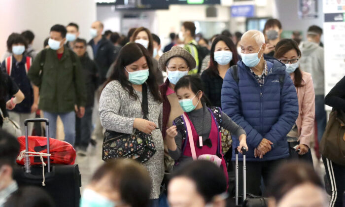 Passengers wearing protective face masks enter the departure hall of a high speed train station in Hong Kong on Jan. 24, 2020. (Achmad Ibrahim/AP Photo)