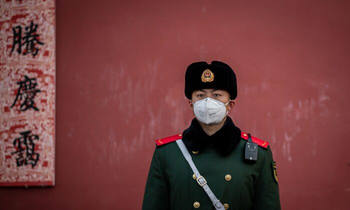 A paramilitary police officer wearing a protective facemask to help stop the spread of a deadly SARS-like virus, which originated in the central city of Wuhan, stands guard at the exit of the Forbidden City in Beijing, China, on Jan. 25, 2020. (Nicolas Asfouri/AFP via Getty Images)