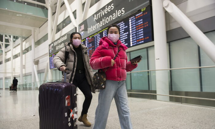 People wear masks as a precaution due to the coronavirus outbreak as they arrive at the International terminal at Toronto Pearson International Airport in Toronto on Jan. 25, 2020. (The Canadian Press/Nathan Denette)