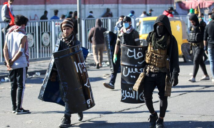 Iraqi protesters with makeshift protective gear walk by following clashes with security forces during an anti-government demonstration in Al-Khilani square in the capital Baghdad, on Jan. 26, 2020. (AHMAD AL-RUBAYE/AFP via Getty Images)
