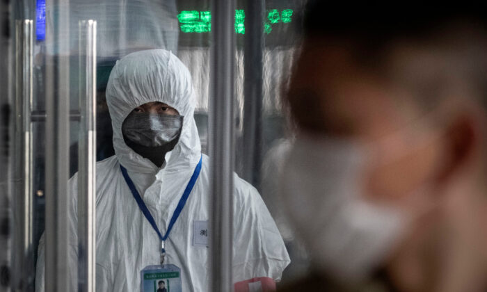 A Chinese health worker waits to check the temperature of travellers entering a train station during the Chinese New Year and Spring Festival in Beijing, China, on Jan. 25, 2020. (Kevin Frayer/Getty Images)