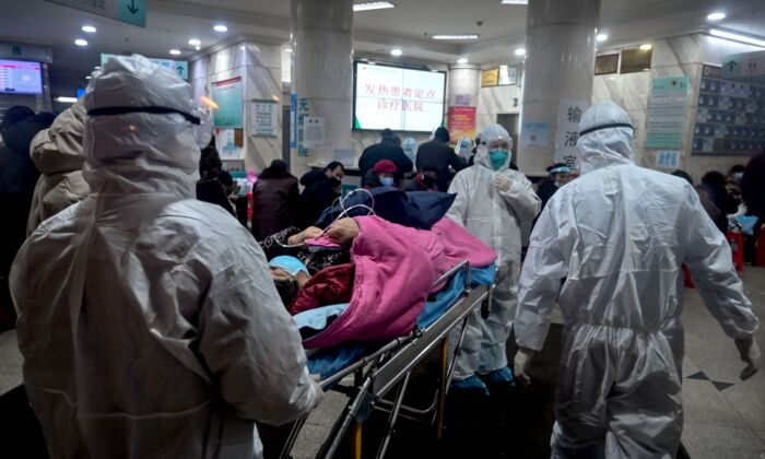 Medical staff wearing protective clothing arrive with a patient at the Wuhan Red Cross Hospital in Wuhan, Hubei Province, China, on Jan. 25, 2020. (Hector Retamal/AFP via Getty Images)