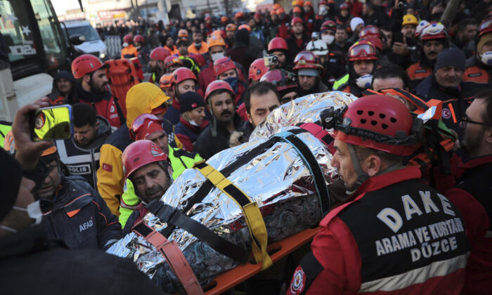 Members of rescue services carry a wounded man, that was found in the rubble of a building destroyed by earthquake, in Elazig, eastern Turkey, on Jan. 25, 2020. (IHH/ Humanitarian Relief Foundation via AP)