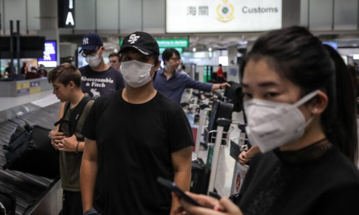 Travellers wearing face masks as a precautionary measure to protect against the outbreak of coronavirus, at Hong Kong International Airport, on Jan. 23, 2020. (Vivek Prakash/AFP via Getty Images)
