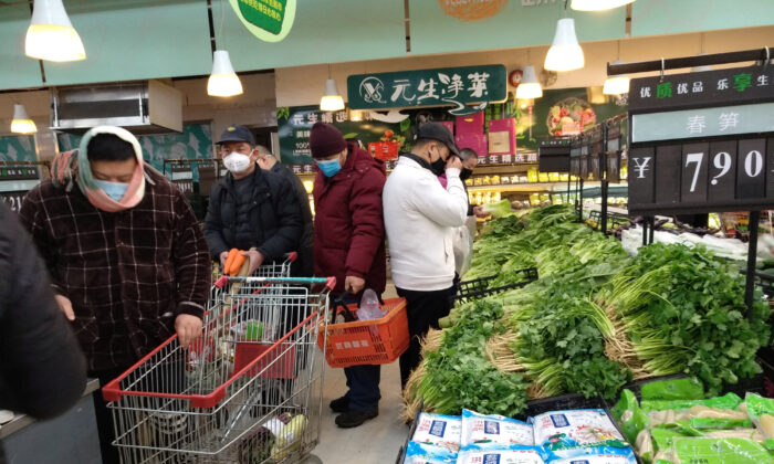 People wearing masks shop at a supermarket on the second day of the Chinese Lunar New Year, following the outbreak of a new coronavirus, in Wuhan, Hubei province, China, on Jan. 26, 2020. (Reuters)