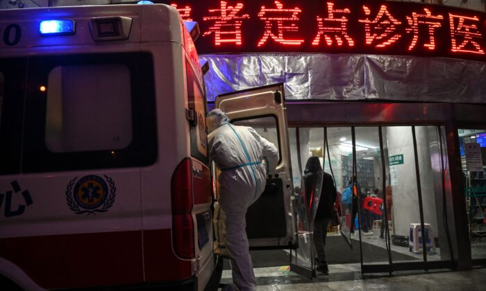 A medical staff member, wearing protective clothing to help stop the spread of a deadly virus that began in the city, boards an ambulance at the Wuhan Red Cross Hospital in Wuhan on Jan. 25, 2020. (Hector Retamal/AFP via Getty Images)