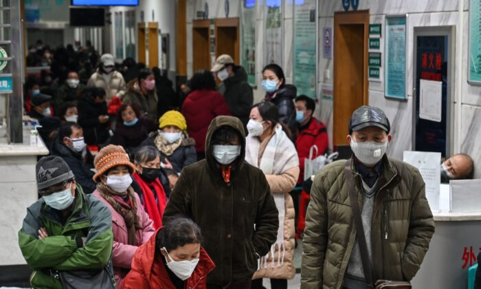 People wearing facemasks to help stop the spread of a deadly virus which began in the city, wait for medical attention at Wuhan Red Cross Hospital in Wuhan, China, on Jan. 25, 2020. (Hector Retamal/AFP via Getty Images)