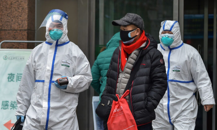 Medical staff wearing clothing to protect against a previously unknown virus walk outside a hospital in Wuhan on Jan. 26, 2020. (Hector Retamal/AFP via Getty Images)