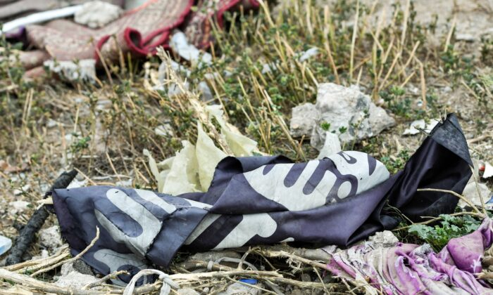 This picture taken shows a discarded Islamic State (IS) group flag lying on the ground in the village of Baghouz in Syria's eastern Deir Ezzor province near the Iraqi border, on March 24, 2019. (Giuseppe Cacace/AFP via Getty Images)