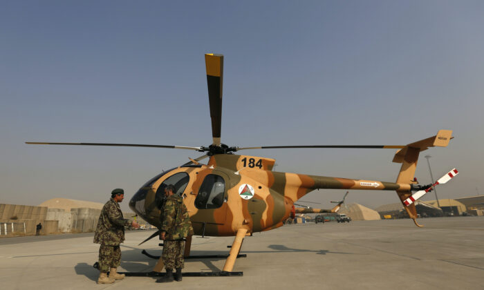 Members of the Afghan Air Force crew stand next to a helicopter at the military airport in Kabul on Dec. 18, 2014. (Mohammad Ismail/Reuters-File)