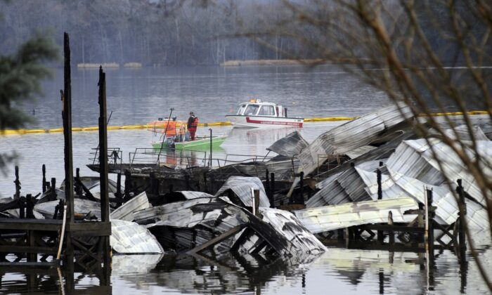 People on boats patrol near the charred remains of a dock following a fatal fire at a Tennessee River marina in Scottsboro, Ala., on Jan. 27, 2020. (Jay Reeves/AP Photo)