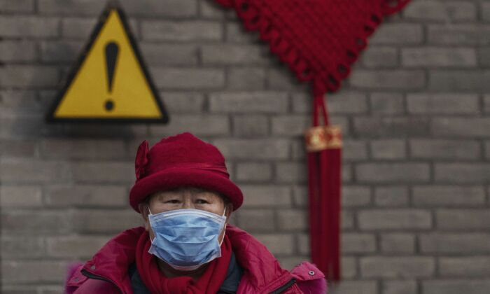 A Chinese visitor wears a protective mask as she was touring the grounds of the Temple of Heaven, which remained open during the Chinese New Year holiday in Beijing, on Jan. 27, 2020. (Kevin Frayer/Getty Images)