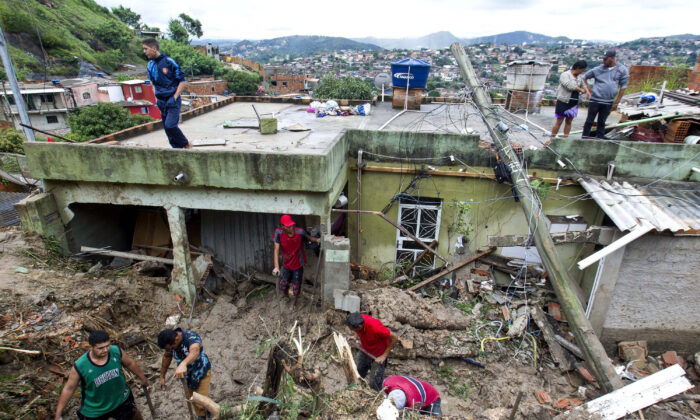 Locals work to clean up mud and debris around houses destroyed by a landslide after heavy rains in the Vila Ideal neighbourhood, Ibirite municipality, Minas Gerias state, Brazil, on Jan. 25, 2020. (Alexandre Mota-Futura Press/ AP Photo)