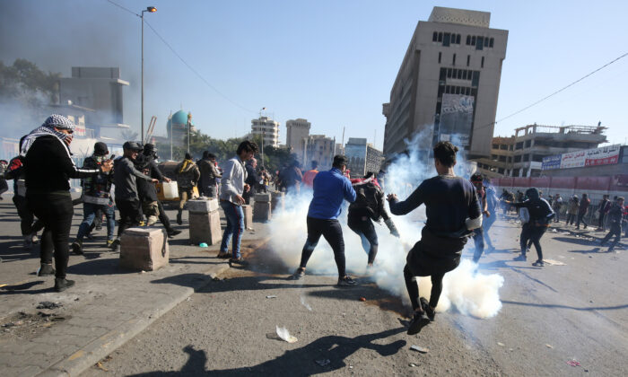 Iraqi protesters scurry to catch a tear gas canister amid clashes with security forces at an anti-regime demonstration in Al-Khillani square in the capital Baghdad, on Jan. 27, 2020. (AHMAD AL-RUBAYE/AFP via Getty Images)