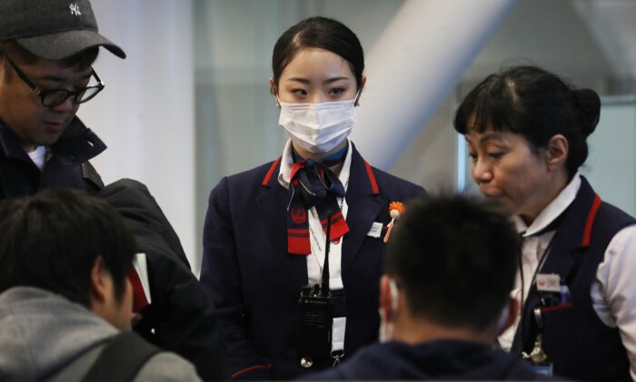 A Japan Airlines worker (C) wears a face mask while working inside a terminal at Los Angeles International Airport (LAX) on Jan. 23, 2020. (Mario Tama/Getty Images)
