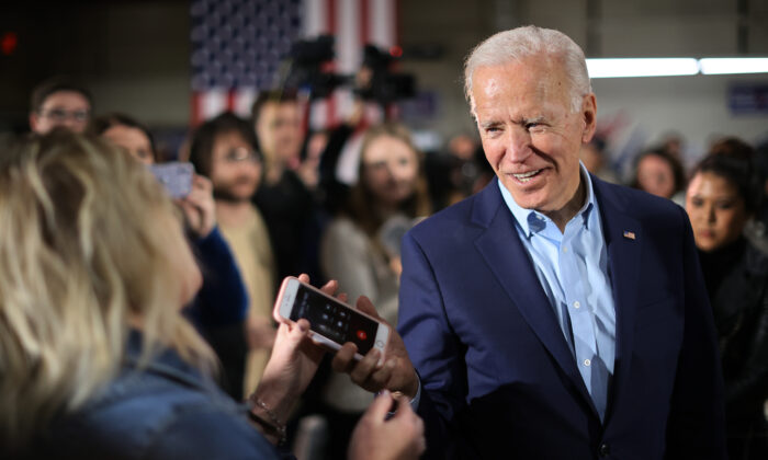 Democratic presidential candidate former Vice President Joe Biden returns a supporter's phone after talking to her relative during a campaign event at the Central Iowa Fairgrounds in Marshalltown, Iowa, on Jan. 26, 2020. (Chip Somodevilla/Getty Images)