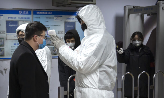 A worker wearing a hazardous materials suit takes the temperature of a passenger at the entrance to a subway station in Beijing on Jan. 26, 2020. (Mark Schiefelbein/AP Photo)