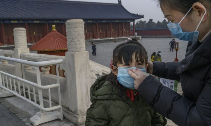 A young Chinese visitor wears a protective mask as she tours the nearly empty grounds of the Temple of Heaven in Beijing, China, on Jan. 27, 2020. (Kevin Frayer/Getty Images)