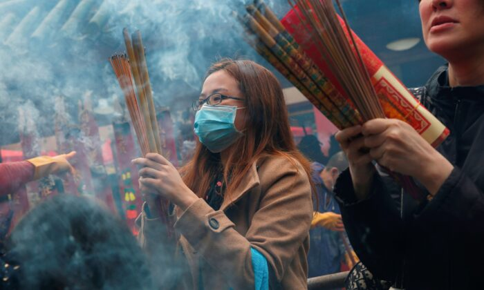 Worshippers wear masks to prevent an outbreak of a new coronavirus as they make offerings of incense sticks during a Lunar New Year celebration at Che Kung Temple, in Hong Kong, China, on Jan. 26, 2020. (Tyrone Siu/Reuters)