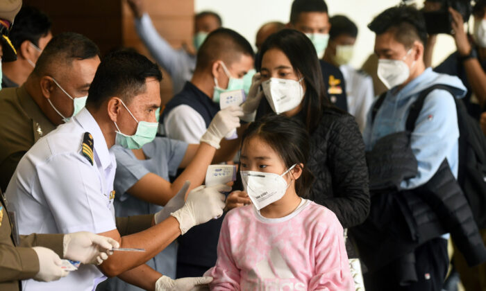 Health workers use infrared thermometers to check the temperature of tourists who arrive at Bangkok's Don Mueang Airport, Thailand, on Jan. 25, 2020. (Panumas Sanguanwong/Reuters)