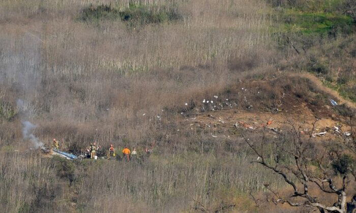 Members of LA County Fire and LA County corners begin the task of removing bodies from the hillside where the helicopter carrying Kobe Bryant and 8 others crashed in Calabasas, Calif., on Jan 26, 2020. (Jayne Kamin-Oncea/USA TODAY Sports via Reuters)