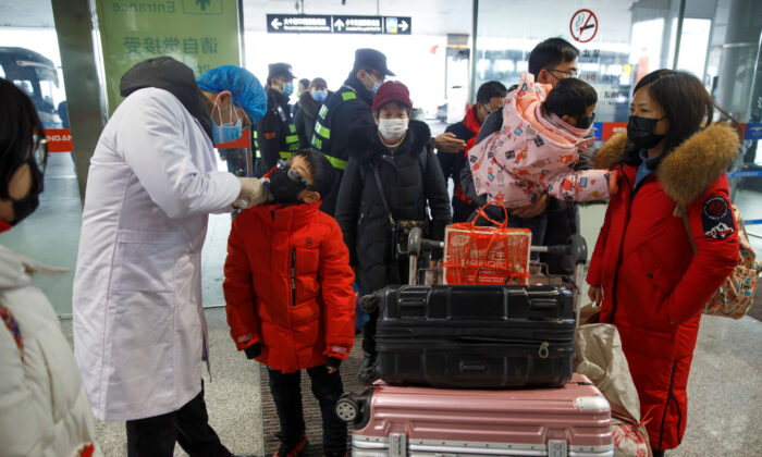 A medical official takes the body temperature of a child at the departure hall of the airport in Changsha, Hunan Province, as the country is hit by an outbreak of a new coronavirus, China, Jan. 27, 2020. (Reuters/Thomas Peter)