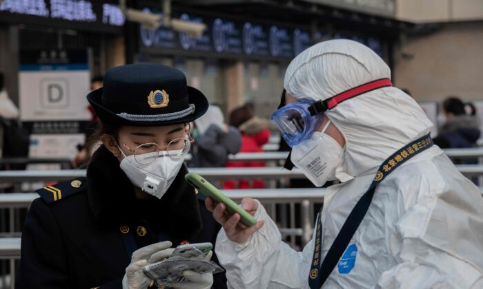 A security personnel wearing protective clothing to help stop the spread of a deadly virus that began in Wuhan, talks with a subway staff (L) wearing a mask at a subway station entrance in Beijing on Jan. 27, 2020. (Nicolas Asfouri/AFP via Getty Images)