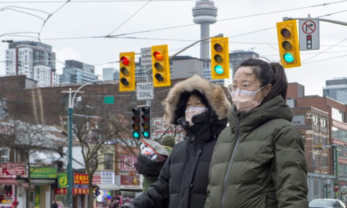 Pedestrians wear protective masks as they walk in Toronto on Jan. 27, 2020. The Canadian government is now advising citizens against all travel to a Chinese province that's at the centre of a global outbreak of a new form of coronavirus, stepping up an earlier warning about the region. (The Canadian Press/Frank Gunn)