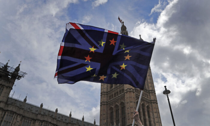 A pro-EU protester waves flags opposite the Houses of Parliament in London on April 4, 2019. (Frank Augstein/AP Photo)