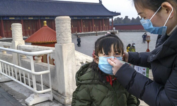 A Chinese woman puts a protective mask on a young girl as they tour the grounds of the Temple of Heaven in Beijing, China, which remained open during the Chinese New Year and Spring Festival holiday on Jan. 27, 2020. (Kevin Frayer/Getty Images)