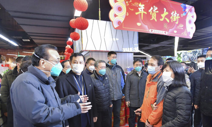 In this photo released by China's Xinhua News Agency, Chinese Premier Li Keqiang (L) speaks with people at a supermarket in Wuhan in central China's Hubei province, on Jan. 27, 2020. (Li Tao/Xinhua via AP)