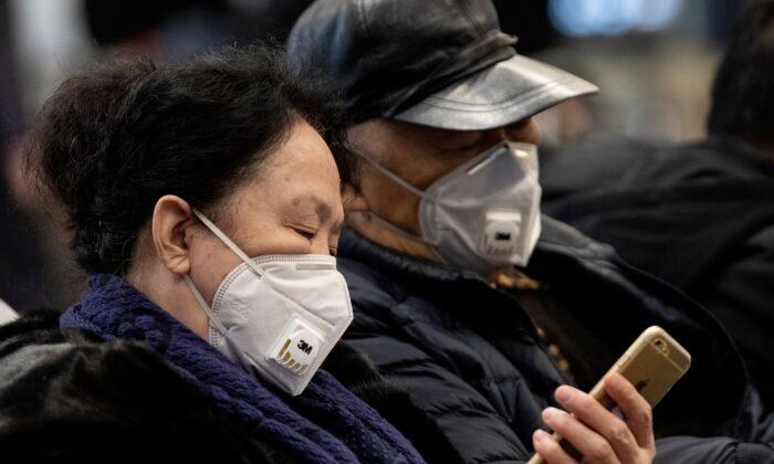 Travellers wearing protective masks rest on a bench after arriving at Beijing Capital Airport in Beijing on Jan. 21, 2020. (NOEL CELIS/AFP via Getty Images)