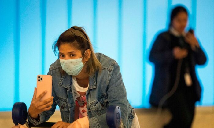 Passengers wear masks to protect against the spread of the Coronavirus as they arrive at the Los Angeles International Airport, California, on Jan. 22, 2020. (Mark Ralston/AFP via Getty Images)