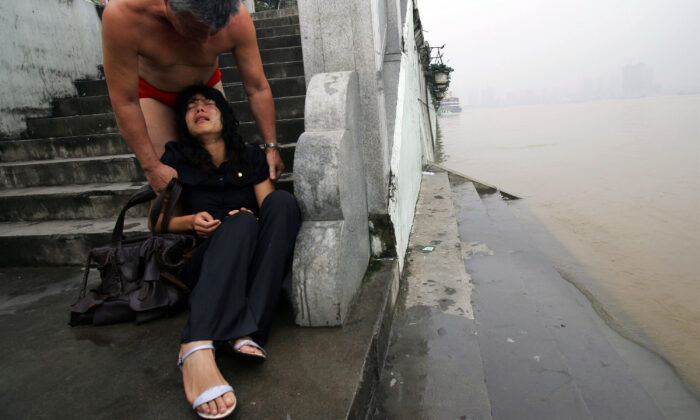 A young woman, who tried to drown herself but was pulled from the water by two swimmers, sits crying as one of the swimmers calms down her at the shore of the Hanjiang River in Wuhan of Hubei Province, China, on July 25, 2007.  China Photos/Getty Images