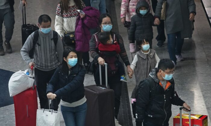 Passengers wear protective face masks arrive at the high speed train station in Hong Kong on Jan. 28, 2020. (Vincent Yu/AP Photo)