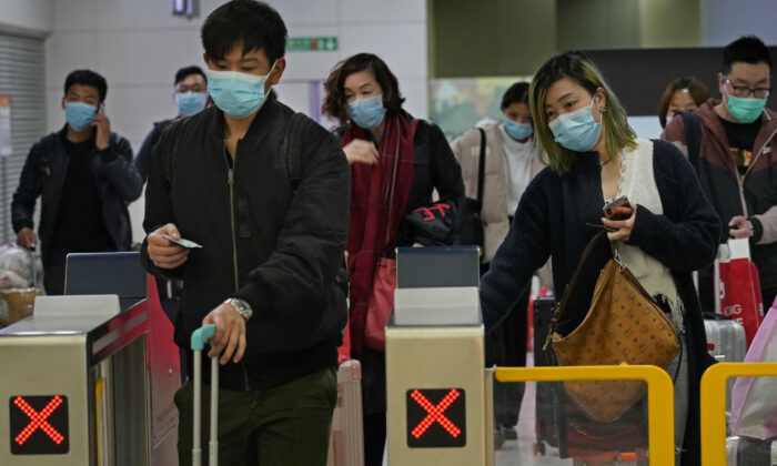 Passengers wearing protective face masks arrive at the high speed train station in Hong Kong on Jan. 28, 2020. Hong Kong's leader has announced that all rail links to mainland China will be cut starting Friday as fears grow about the spread of a new virus. (Vincent Yu/AP Photo)