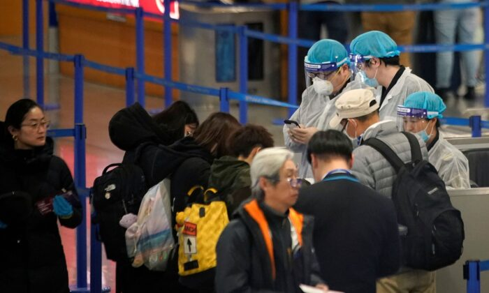 Medical officials are seen as passengers leave at the Pudong International Airport in Shanghai, China, on Jan. 27, 2020. (Aly Song/Reuters)