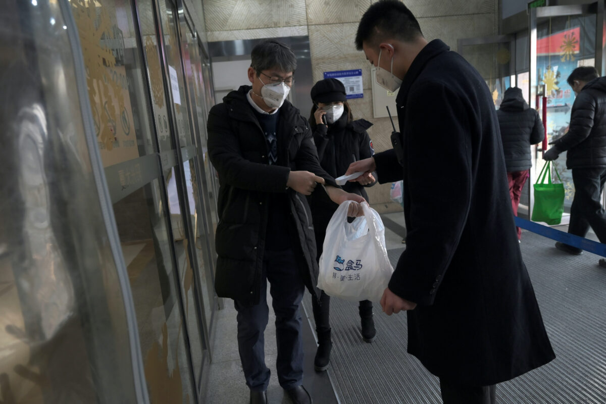 Security personnel checks temperature of a customer entering Alibaba's Hema Fresh chain store, following the coronavirus outbreak, in Beijing