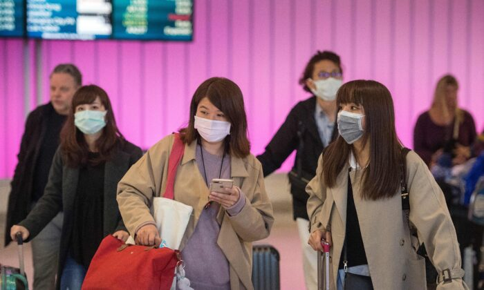 Passengers wear protective masks to protect against the spread of the Coronavirus as they arrive at the Los Angeles International Airport, Calif., on Jan. 22, 2020. (Mark Ralston/AFP via Getty Images)