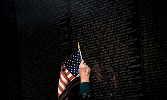 A man points to a name while visiting the Vietnam War Memorial on Veterans Day in Washington on Nov. 10, 2017.  Brendan Smialowski/AFP via Getty Images