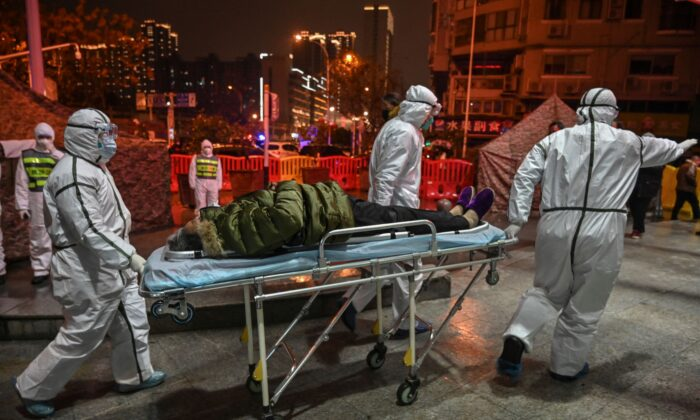 Medical staff members wearing protective clothing to help stop the spread of a deadly virus which began in the city, arrive with a patient at the Wuhan Red Cross Hospital in Wuhan, China, on Jan. 25, 2020. (Hector Retamal/AFP via Getty Images)