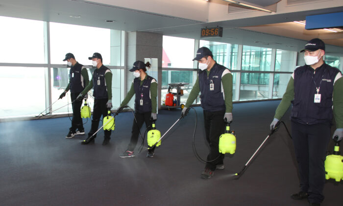 Employees from a disinfection service company sanitize the floor of Incheon International Airport in Incheon, South Korea, on Jan. 24, 2020. (Yonhap via Reuters)