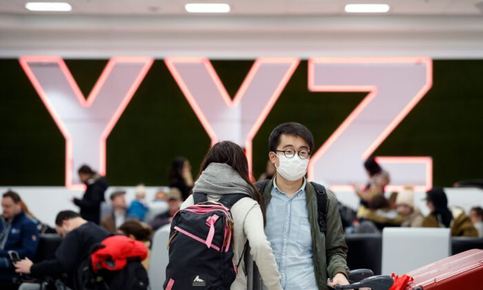 Travelers are seen wearing masks at the international arrivals area at the Toronto Pearson Airport in Toronto, Canada, on Jan. 26, 2020. (Cole Burston/AFP via Getty Images)