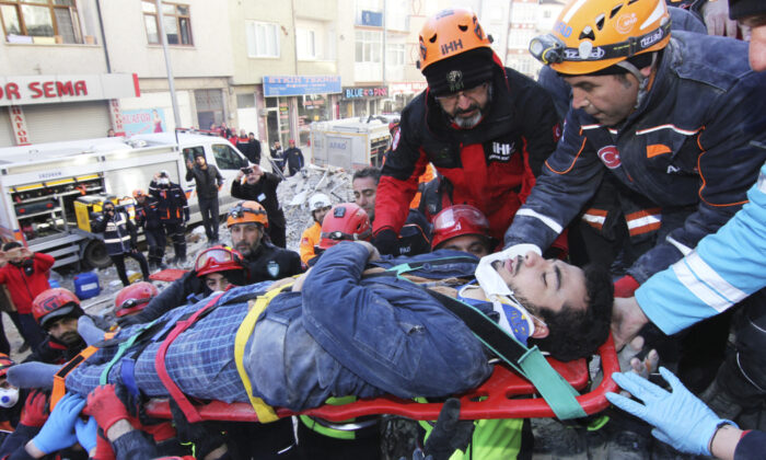 Rescue workers carry a wounded man that was found alive in the rubble of a building destroyed on Friday's earthquake in Elazig, eastern Turkey, Saturday, Jan. 25, 2020. (Depo Photos via AP)